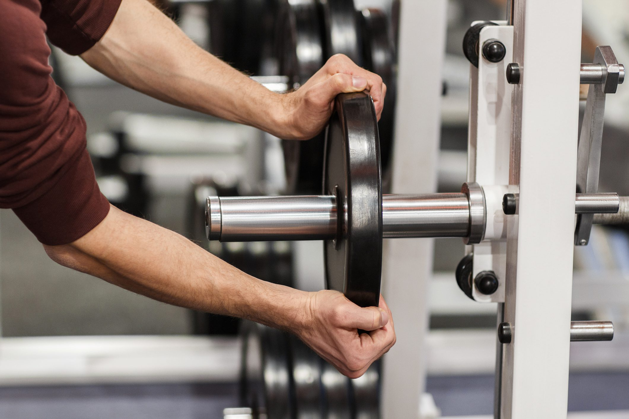 Male hand putting weight plate on barbell